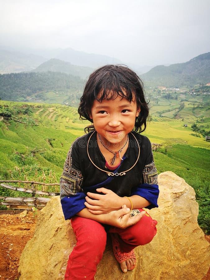 Retrato de una pequeña muchacha de la minoría de Hmong (Miao) que se sienta en una roca fotografía de archivo