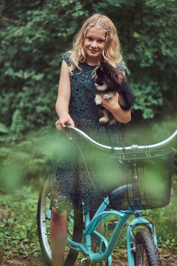 Retrato de una pequeña muchacha rubia en una ropa informal, perro lindo del perro de Pomerania de los controles, en un parque fotografía de archivo libre de regalías
