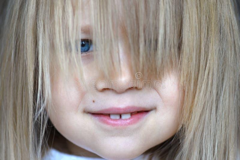 Retrato de una pequeña muchacha sonriente con su pelo flojamente en su cara fotos de archivo