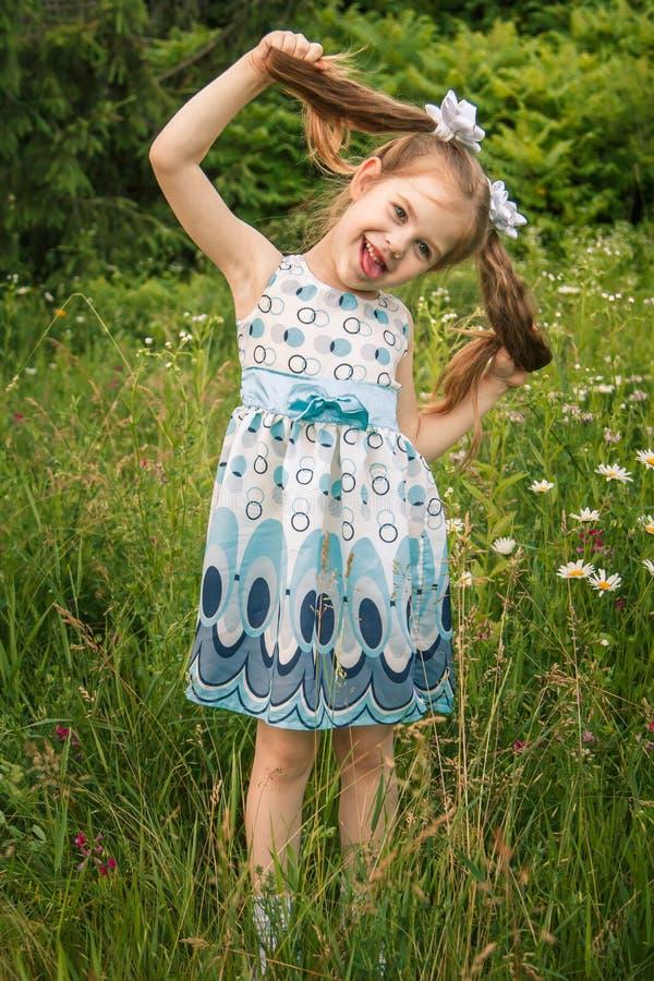 Retrato de una peque?a muchacha pelirroja Ella está en el parque en los rayos del sol poniente fotografía de archivo libre de regalías