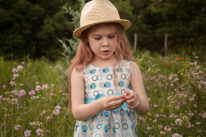 Retrato de una peque?a muchacha pelirroja Ella está en el parque en los rayos del sol poniente imagenes de archivo
