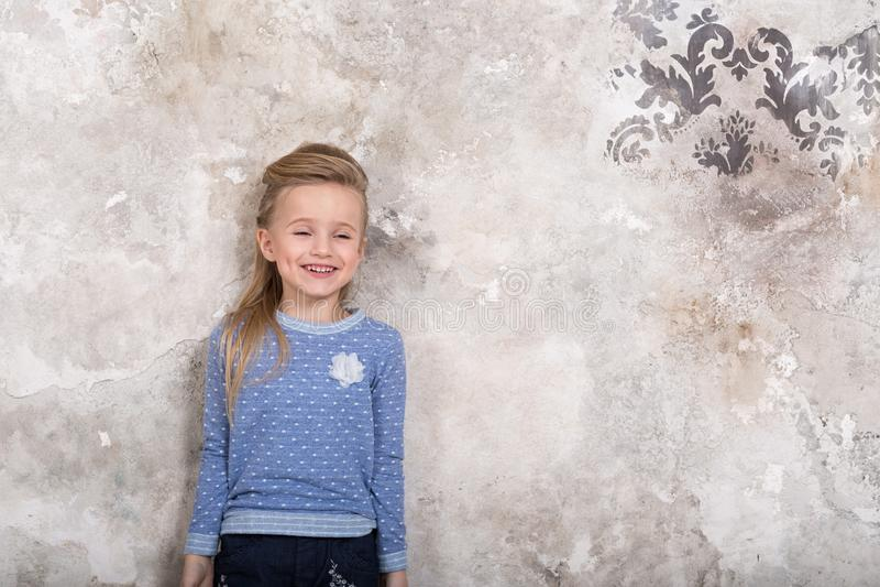 Retrato de una peque?a muchacha sonriente atractiva en un su?ter azul y pantalones con el pelo doblado en su pelo contra una pare imágenes de archivo libres de regalías
