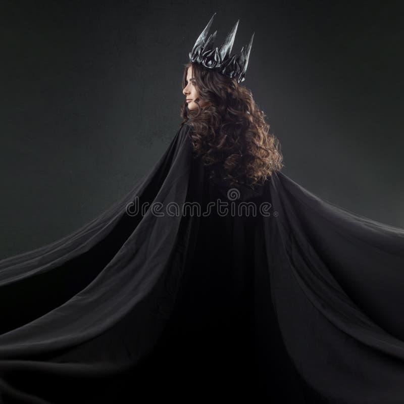 Retrato de una princesa gótica Mujer morena joven hermosa en corona del metal y capa negra foto de archivo libre de regalías