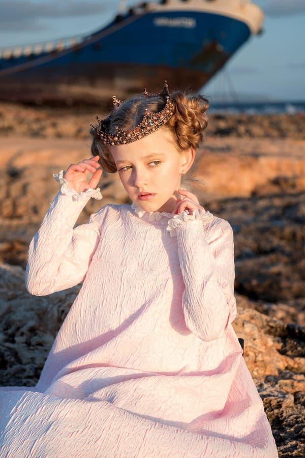Retrato de una princesa nerviosa en un vestido rosado y en una corona que se sienta en una roca cerca de una nave rota en el mar foto de archivo
