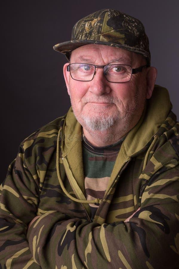 Retrato de una ropa mayor mayor y de vidrios del camuflaje del viejo hombre que lleva la cara del jubilado es feliz y sonrisa imágenes de archivo libres de regalías
