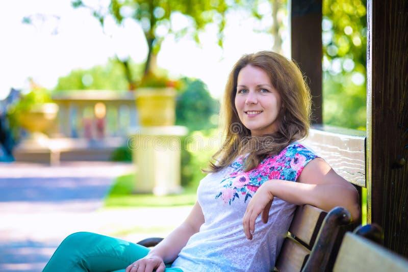 Retrato de una señora bastante pensativa que se sienta en banch en parque con colores artísticos y de las sombras añadidas foto de archivo libre de regalías
