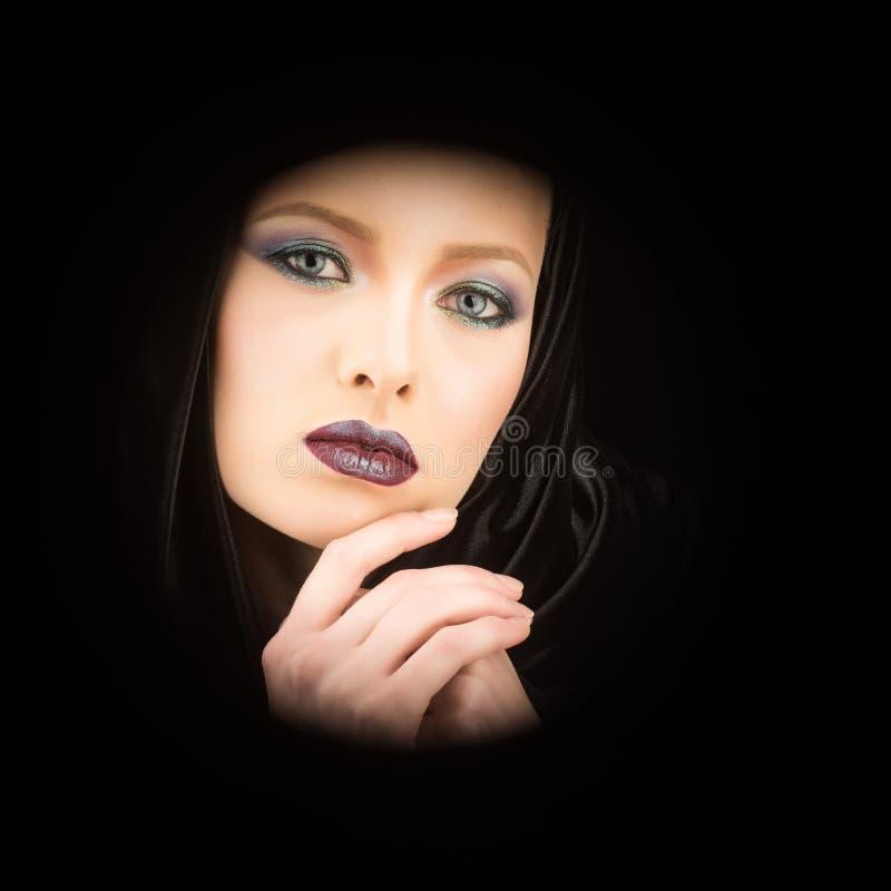 Retrato de una señora bonita que lleva una capa encapuchada negra gótica actitud contra un fondo negro fotografía de archivo