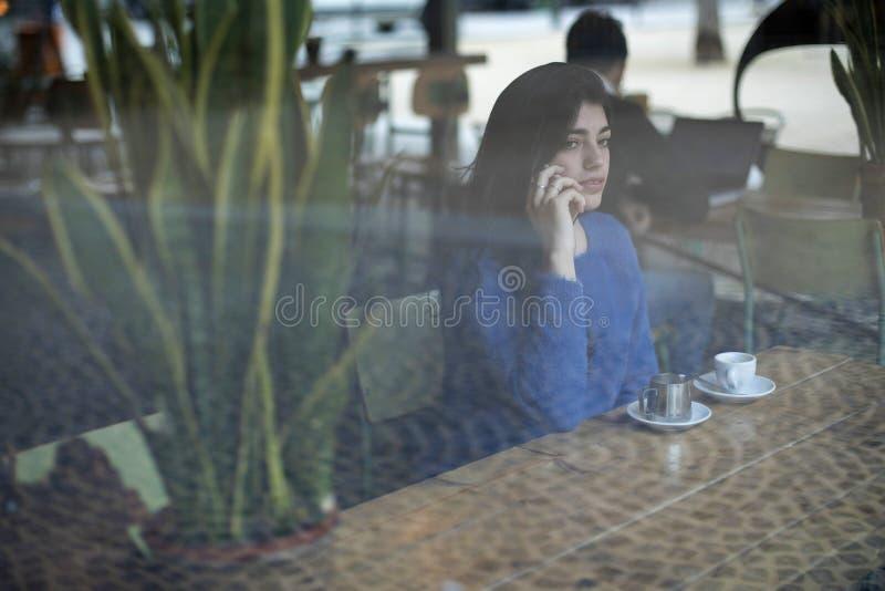 Retrato de una señora joven hermosa usando smartphone y la mirada del vidrio lejos directo mientras que se sienta en la tabla en  foto de archivo