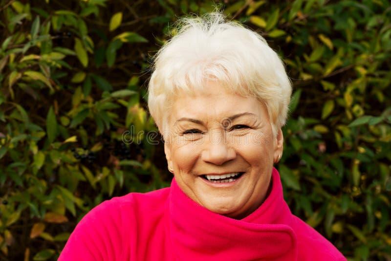 Retrato de una señora mayor alegre sobre fondo verde. fotos de archivo