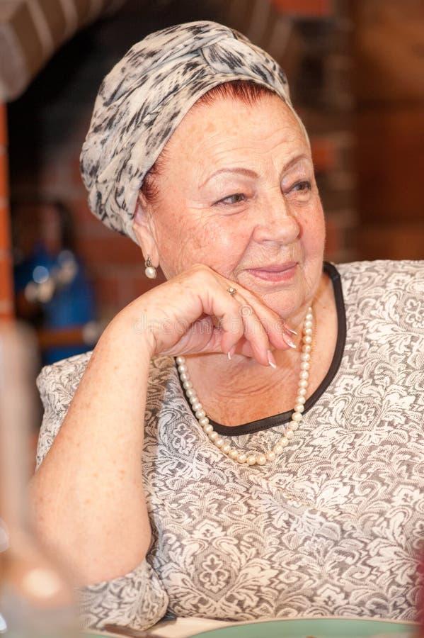 Retrato de una señora mayor elegante que se sienta en la tabla del día de fiesta foto de archivo