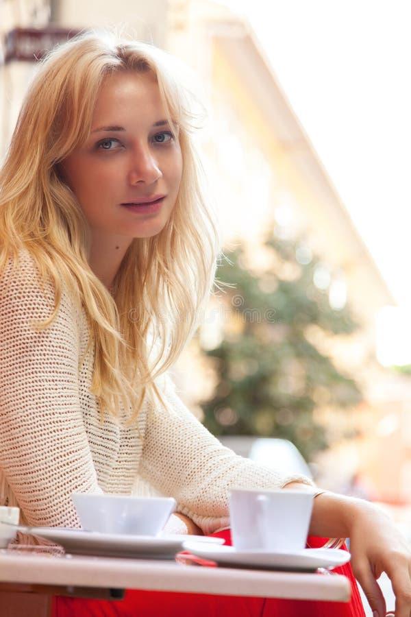 Retrato de una señora rubia joven linda que se sienta en café fotografía de archivo libre de regalías