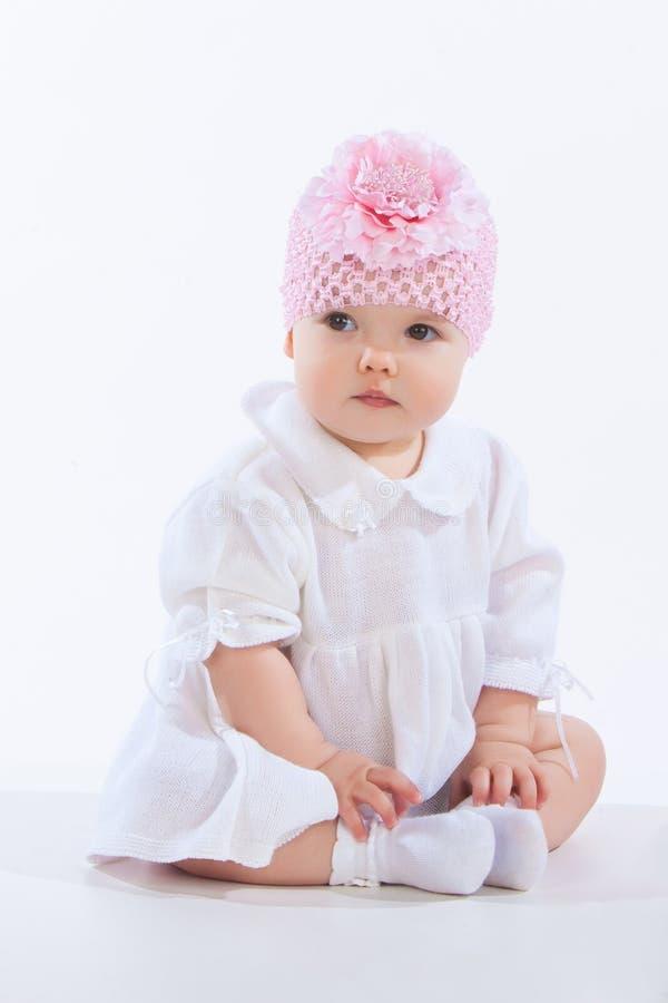 Retrato de una sentada de la niña, aislado en el fondo blanco imagen de archivo