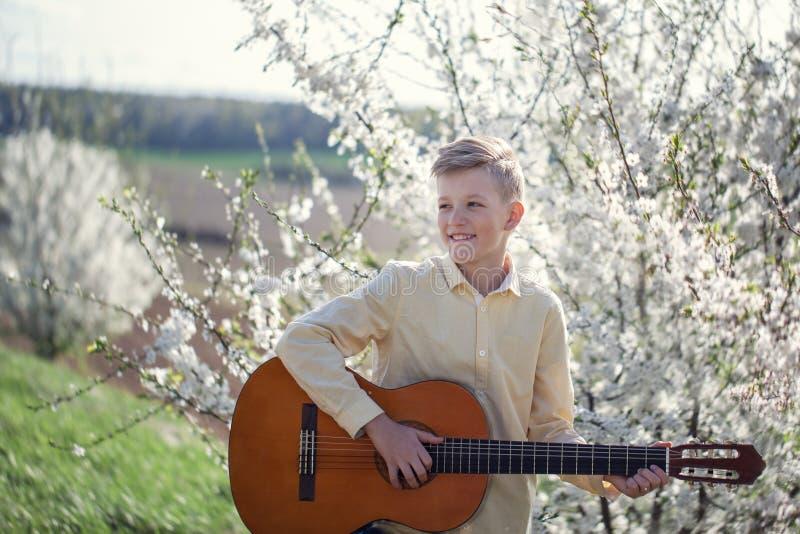 Retrato de una situación de 11 años joven del muchacho en parque de la primavera y guitarra el jugar imagen de archivo