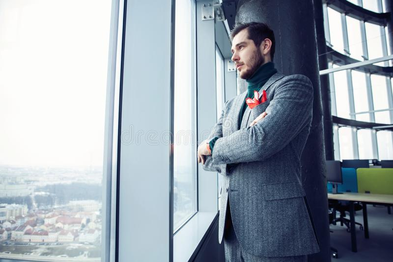 Retrato de una situaci?n joven ocasional vestida del hombre de negocios en una oficina de moda fotografía de archivo libre de regalías