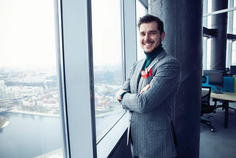 Retrato de una situaci?n joven ocasional vestida del hombre de negocios en una oficina de moda fotografía de archivo