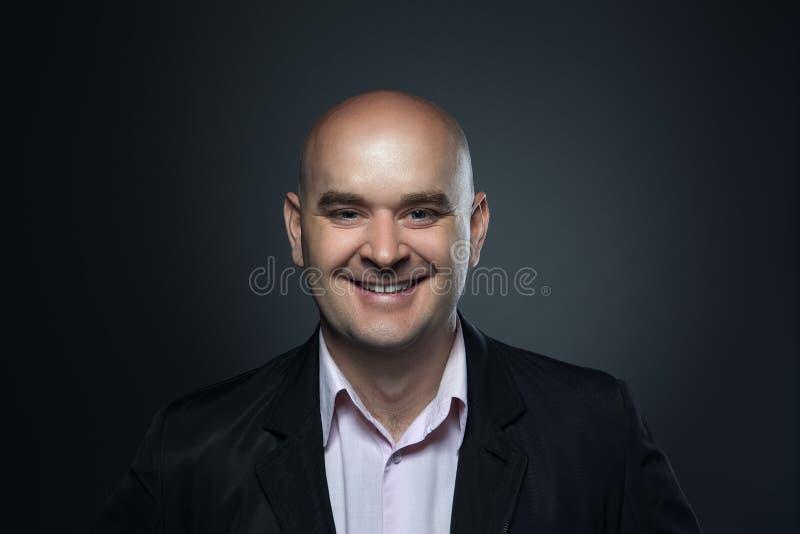 Retrato de una sonrisa calva, hombre afable en un traje contra un fondo oscuro foto de archivo libre de regalías
