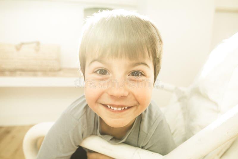 Retrato de una sonrisa y de un niño feliz en casa Niño con la expresión alegre fotos de archivo libres de regalías
