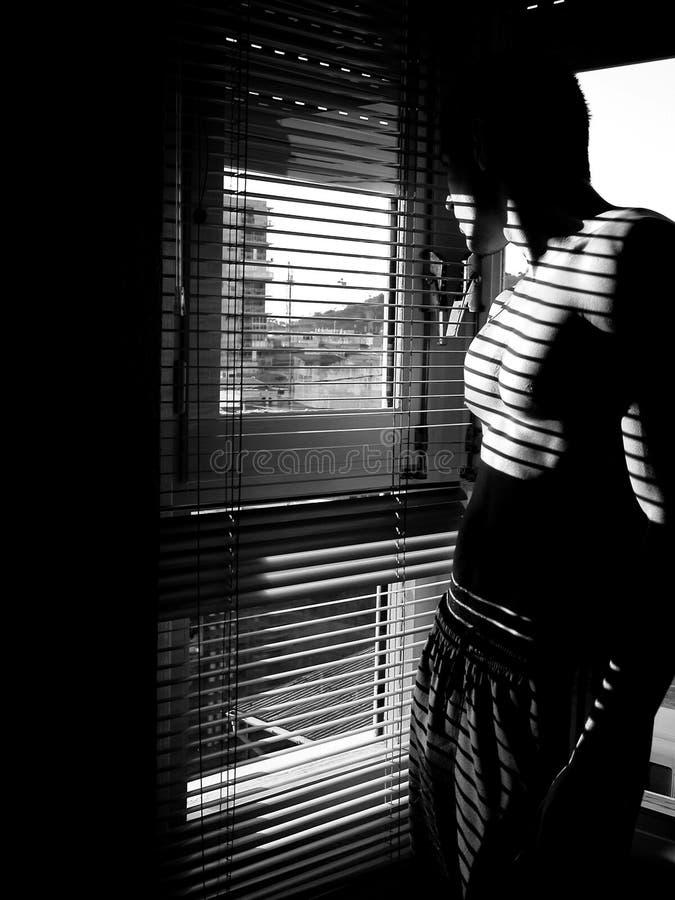 Retrato de uno mismo de descamisado modelo masculino y de mirar hacia fuera una ventana