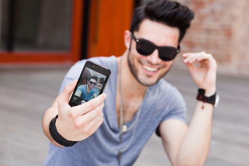 Retrato de uno mismo de fabricación masculino joven con un smartphone imagen de archivo