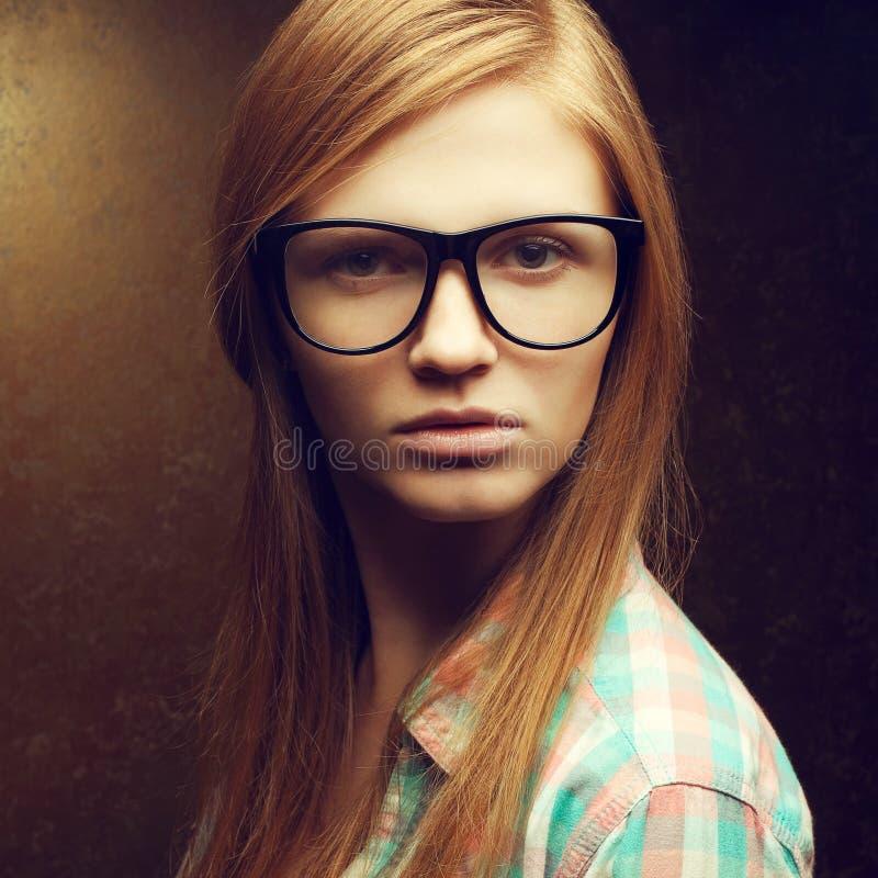Retrato de vidrios de moda que llevan pelirrojos hermosos jovenes imagen de archivo