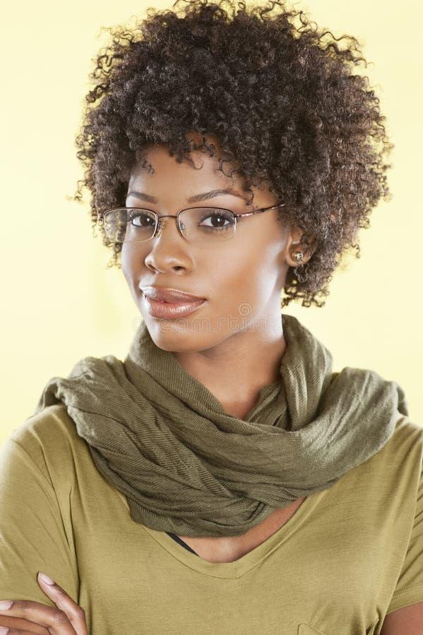 Retrato de vidros vestindo de uma mulher afro-americano esperta com uma estola redonda seu pescoço sobre o fundo colorido imagem de stock royalty free
