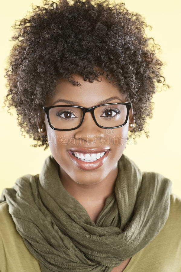 Retrato de vidros vestindo de uma mulher afro-americano feliz com uma estola redonda seu pescoço sobre o fundo colorido foto de stock
