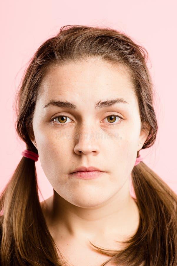 Definiti alto dos povos reais sérios do fundo do rosa do retrato da mulher fotografia de stock