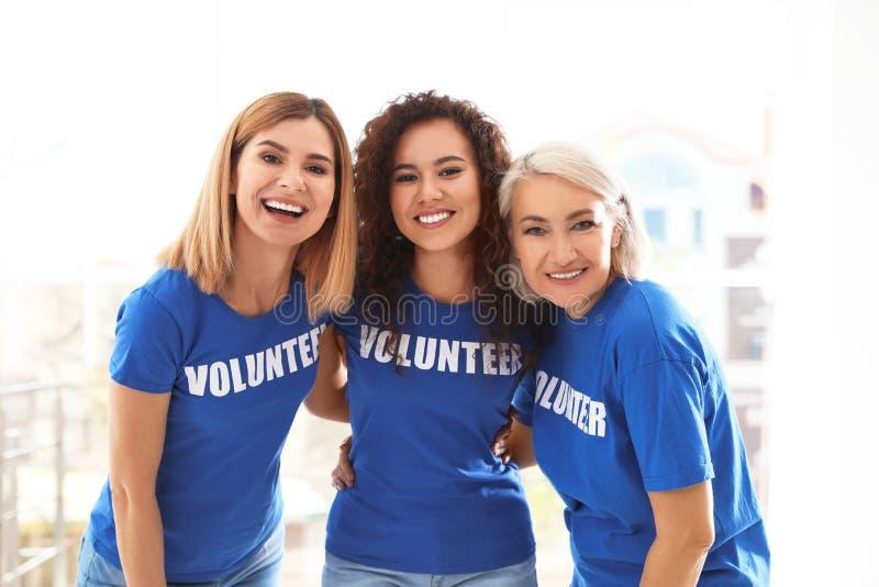 Retrato de voluntários fêmeas felizes no uniforme fotografia de stock royalty free