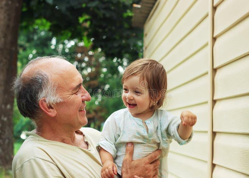 Retrato del abuelo feliz y del grandaughter que juegan en el GA imágenes de archivo libres de regalías