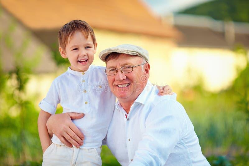 Retrato del abuelo feliz y del nieto que abrazan al aire libre imagenes de archivo