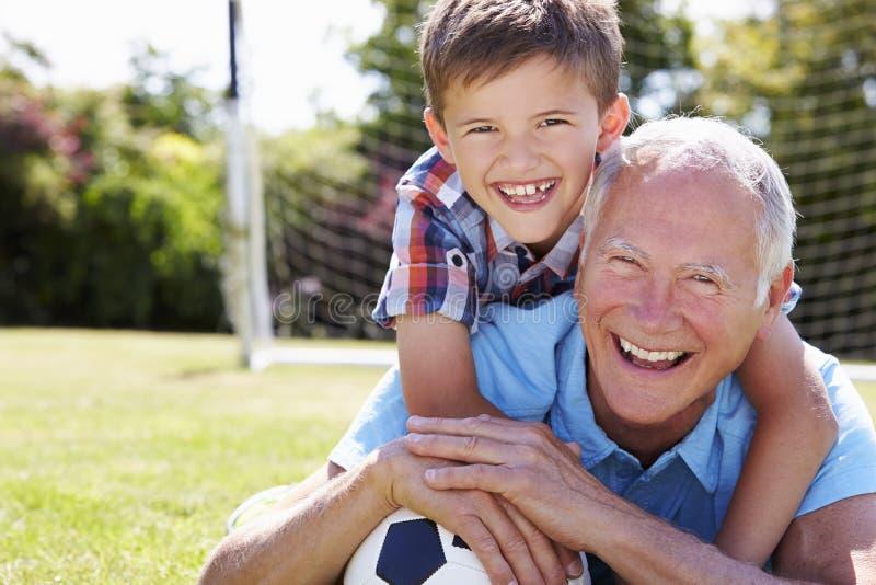Retrato del abuelo y del nieto con fútbol imagenes de archivo