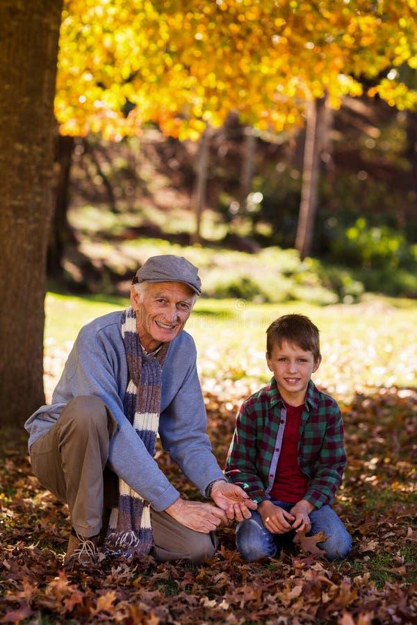 Retrato del abuelo y del nieto que juegan con las hojas de otoño fotos de archivo