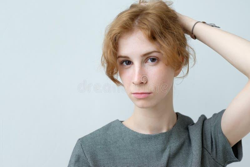 Retrato del adolescente blando joven del pelirrojo con la piel pecosa sana que lleva el vestido oficial que mira la cámara foto de archivo
