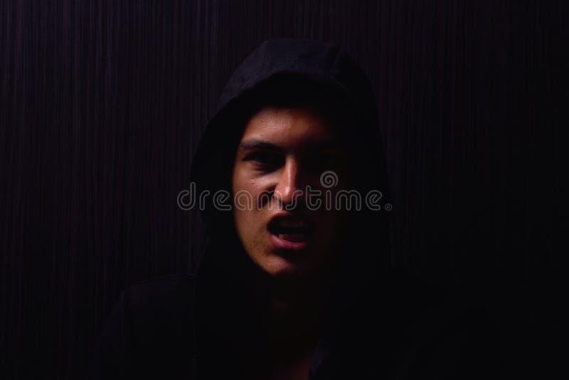 Retrato del adolescente con la expresión seria y la sudadera con capucha negra imágenes de archivo libres de regalías