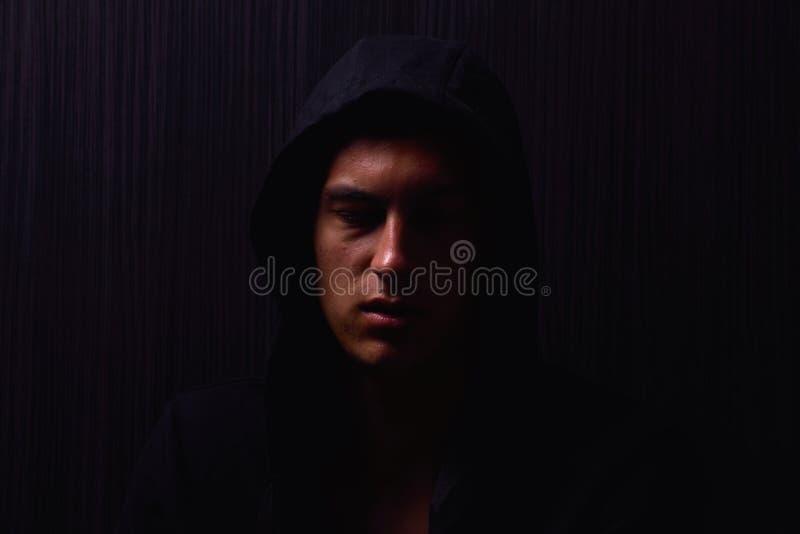 Retrato del adolescente con la expresión seria y la sudadera con capucha negra fotos de archivo libres de regalías