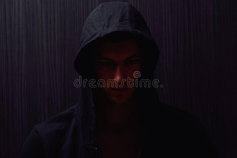 Retrato del adolescente con la expresión seria y la sudadera con capucha negra fotografía de archivo libre de regalías