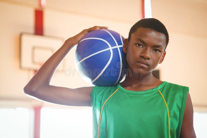 Retrato del adolescente confiado que lleva a cabo baloncesto foto de archivo libre de regalías