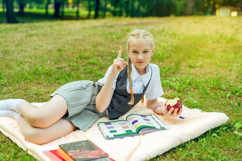 Retrato del adolescente de la colegiala con las coletas que se sientan en parque en la sobrecama con la manzana imagenes de archivo