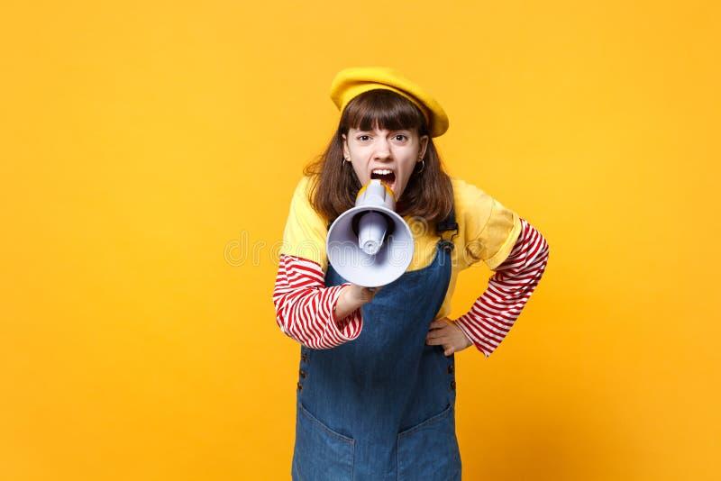 Retrato del adolescente enojado de la muchacha en la boina francesa, grito en megáfono, el jurar de los sundress del dril de algo foto de archivo libre de regalías