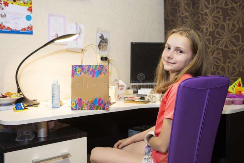 Retrato del adolescente femenino caucásico con la mano herida en el yeso Presentación delante de la tabla dentro imágenes de archivo libres de regalías