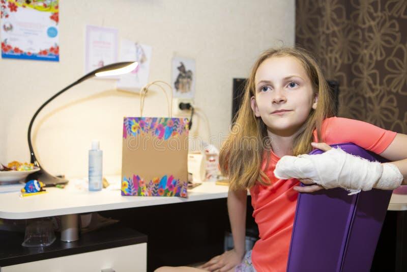 Retrato del adolescente femenino caucásico con la mano herida en el yeso Presentación delante de la tabla dentro imagen de archivo