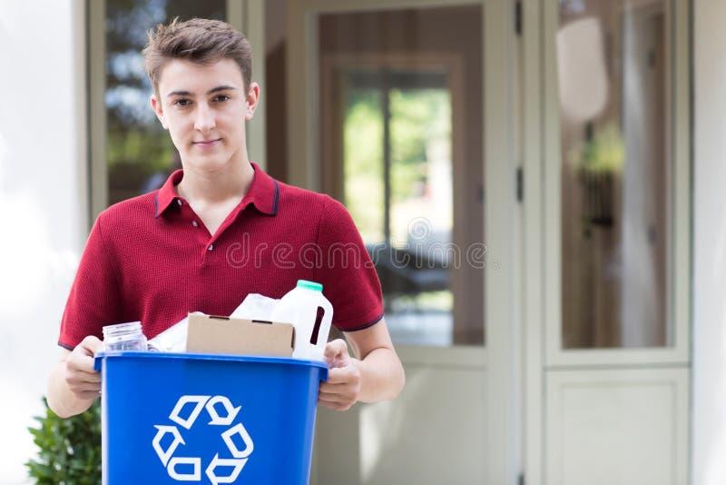 Retrato del adolescente fuera de la papelera de reciclaje que lleva de la casa imagen de archivo