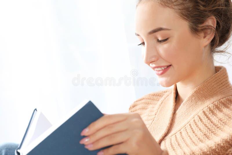 Retrato del adolescente hermoso en libro de lectura acogedor caliente del suéter cerca de la ventana fotos de archivo libres de regalías
