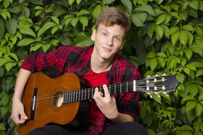 Retrato del adolescente hermoso que toca la guitarra afuera imágenes de archivo libres de regalías
