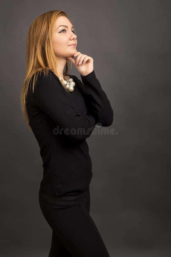 Retrato del adolescente pensativo que lleva a cabo la mano en la barbilla y la mirada fotografía de archivo