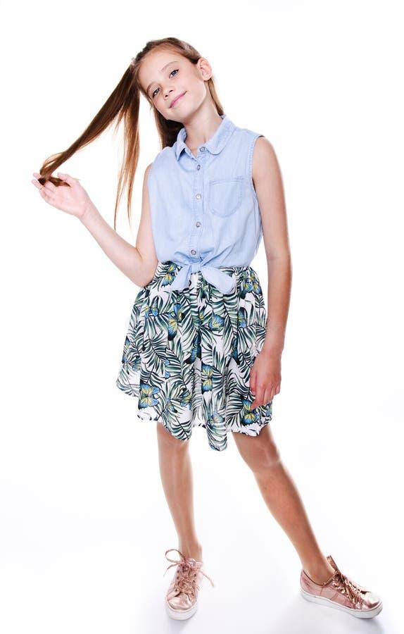 Retrato del adolescente sonriente adorable de la colegiala del niño de la niña en vestido con el pelo largo que se coloca aislado imágenes de archivo libres de regalías