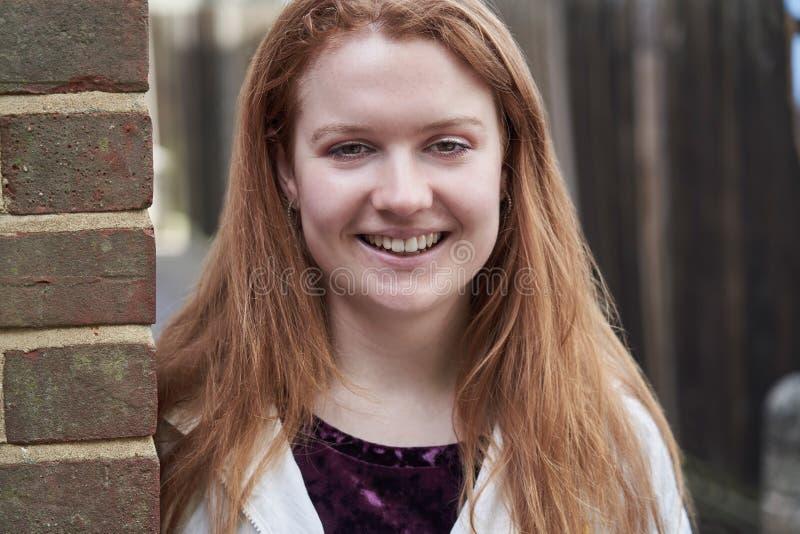 Retrato del adolescente sonriente que se inclina contra la pared en el ambiente urbano foto de archivo