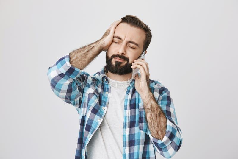 Retrato del adulto joven cansado y perplejo con los ojos del closing de la barba y del bigote y la mano de la tenencia en la cabe imagenes de archivo