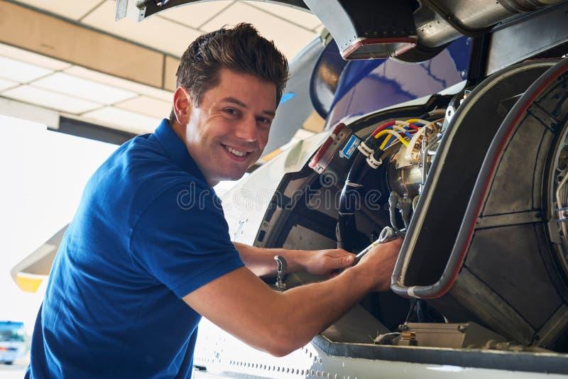 Retrato del aero- ingeniero de sexo masculino Working On Helicopter en hangar fotos de archivo