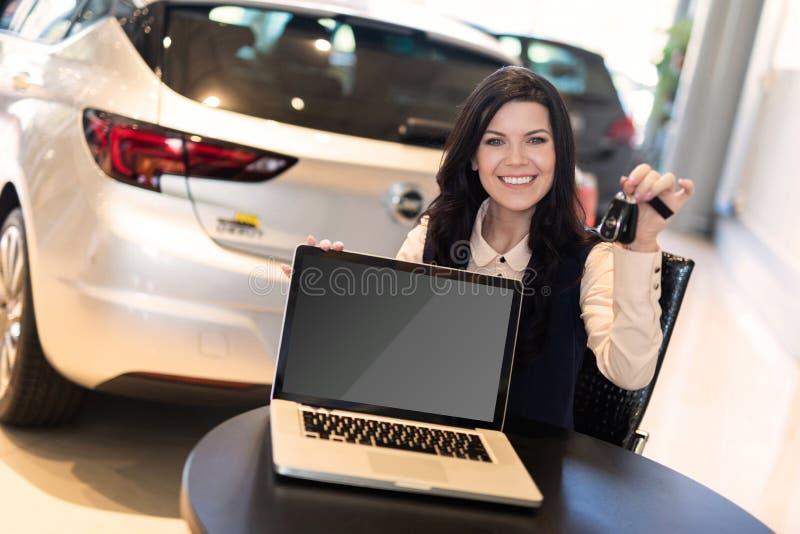 Retrato del agente de seguro smilling hermoso que se sienta cerca del nuevo coche imagenes de archivo